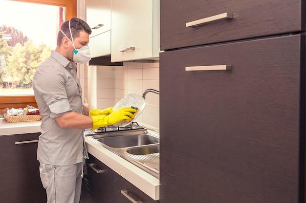 防護マスクを持つ男は家で皿を掃除します。