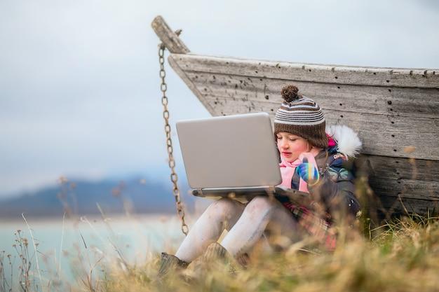 Молодая девушка сидит в траве и с помощью портативного компьютера