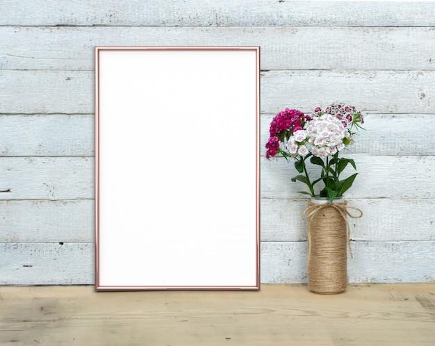 甘いウィリアムの花束の近くのローズゴールドの垂直フレームが木製のテーブルの上に立つ