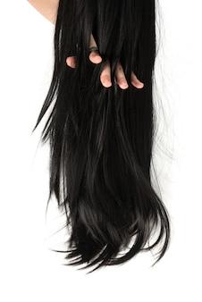 Черные волосы в руке женщины изолированы.