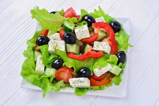白い木製のテーブルのギリシャ風サラダ