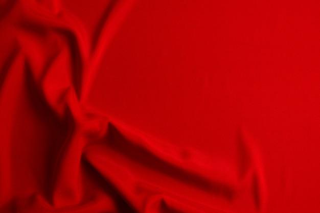 赤い絹またはサテンの高級生地のテクスチャは、抽象的な背景として使用できます。上面図