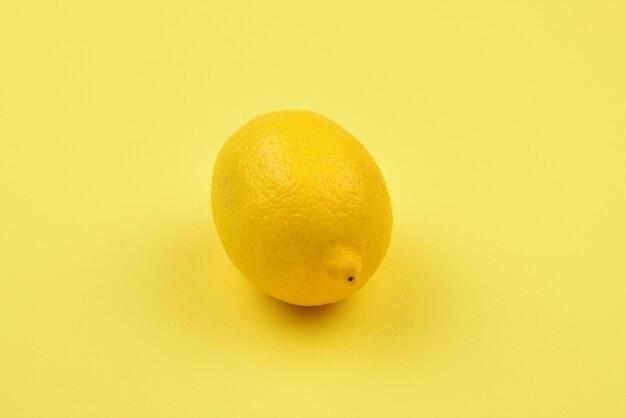 黄色の背景に分離されたレモン。テストまたは設計のためのスペース。