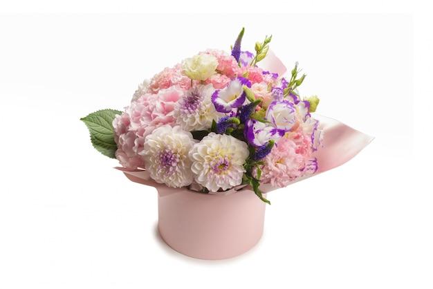 白い背景に分離されたピンクのボックスに花のピンクと紫の花束。