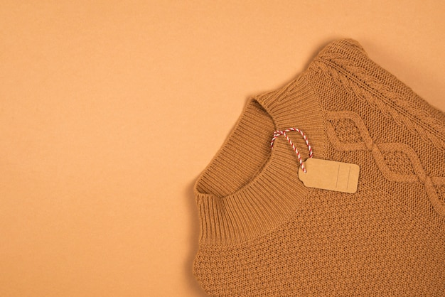 Коричневая бирка на коричневом вязаном свитере.