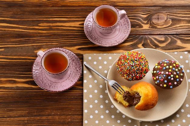 Выпечка с чаем и шоколадом на столе. две чашки чая с кексы и шоколад с разноцветной пудрой на столе.