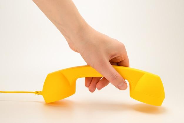 白で隔離される女性の手で黄色の携帯電話。