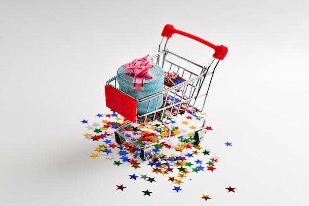 ショッピングカートと紙吹雪でピンクの弓と青いプレゼントボックス