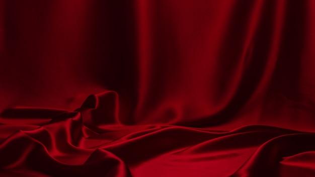赤い絹またはサテンの高級生地のテクスチャ