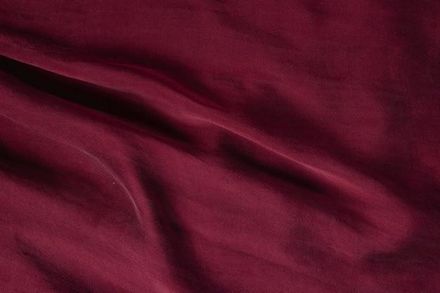Мягкая гладкая бордовая шелковая ткань фона. текстура ткани.