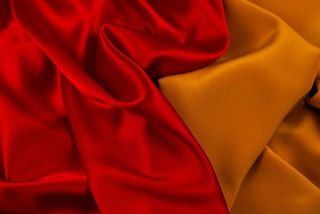 赤とオレンジのシルクまたはサテンの豪華な生地のテクスチャは、抽象的な背景として使用できます。