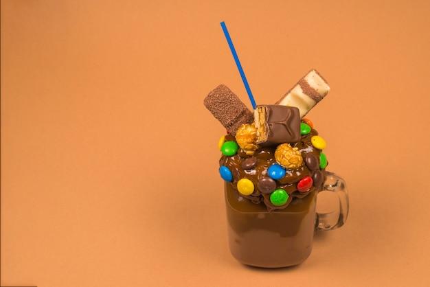 Шоколадный молочный коктейль со взбитыми сливками, печеньем, вафлями, подается в стеклянной банке.