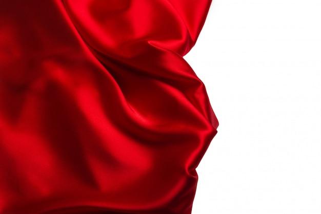 赤い絹またはサテンの豪華な生地のテクスチャは抽象的な背景として使用できます。