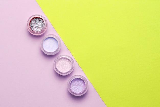 化粧品。化粧。ぼろぼろの明るい影、輝きのある瓶。薄紫色の背景にピンク、グリーン、ライラック色。閉じる。テキストまたはデザインのためのスペース。