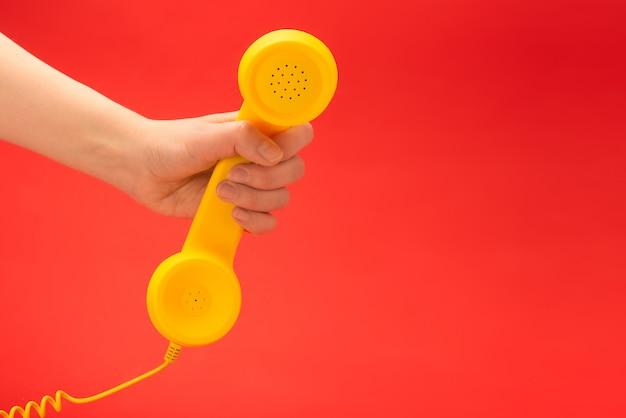 Желтая телефонная трубка на красной предпосылке в руке женщины.