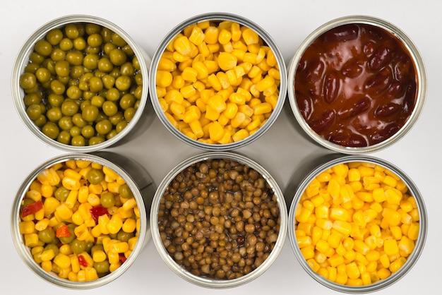 白い背景の上の缶詰。グリーンピース、豆、トウモロコシ、レンズ豆。