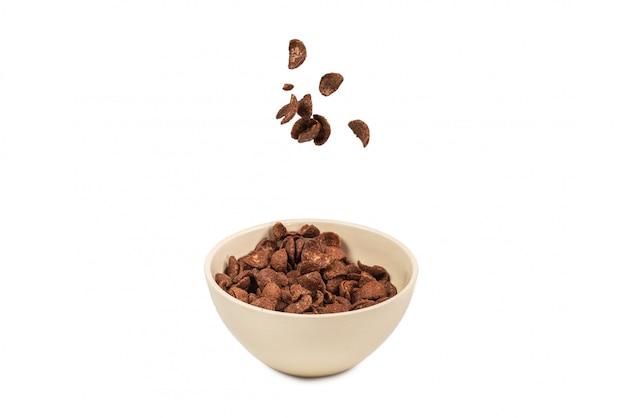 白で隔離される白いボウルに落ちるチョコレートコーンフレーク。モーション。