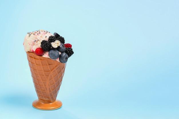 ブルーベリー、ブラックベリー、青色の背景にラズベリーのアイスクリーム。
