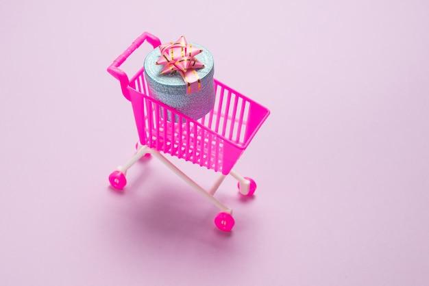 Синяя подарочная коробка с розовым бантом в корзине