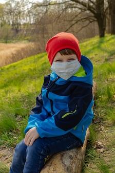医療マスクのかわいい男の子は、ログの丘の上に座って、湖を見てください。家族は検疫中に春先に屋外で子供と一緒に歩く