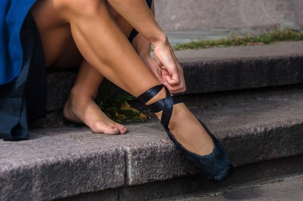 エレガントな女性ダンサーが階段に座って、黒いトウシューズをドレスアップ