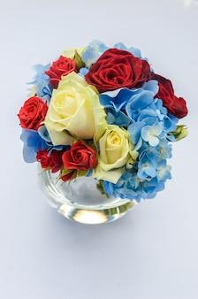Красивый свежий яркий букет из синих гортензий, красных и кремовых роз в стеклянной круглой вазе на белом столе. красивая цветочная композиция.