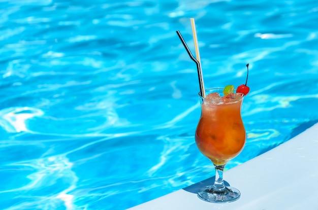 青いプールの端にあるオレンジ色の飲み物のグラス。
