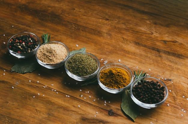 Разнообразие специй в круглых стеклянных мисках. молотый имбирь, хмель-сунели, кари, черный перец и микс