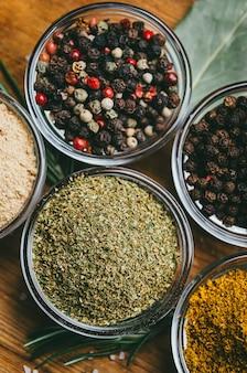 Разнообразие специй в круглых стеклянных мисках. молотый имбирь, хмель-сунели, кари, черный перец и смесь.