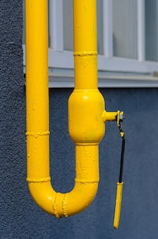 多階建ての建物のファサードに通気口のある黄色のガス管。家庭用天然ガス、ガス配管。