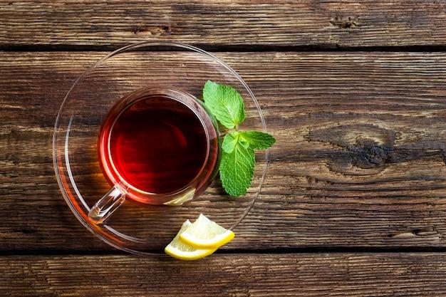 Стеклянная чашка с чаем, мятой и лимоном на деревянной деревенской предпосылке. вид сверху с копией пространства.