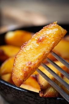 フォークのクローズアップに焼きたてのジャガイモのスライス