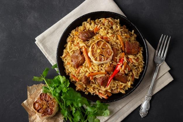 オリエンタル料理。木製の素朴なボード上の鋳鉄鍋にご飯と肉からウズベキスタンのピラフまたはプロヴ。
