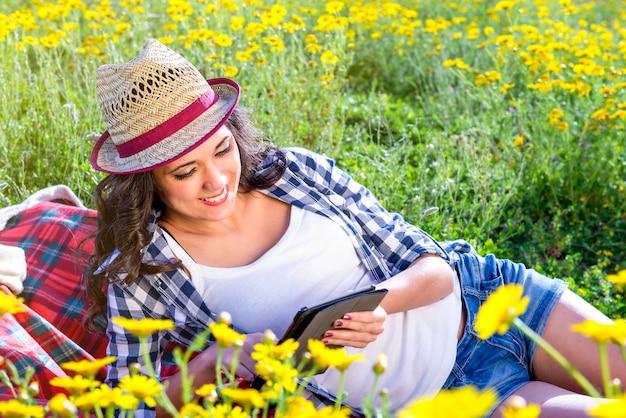 Девушка читает планшет на природе