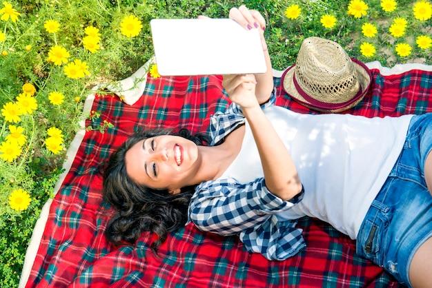 Счастливая девушка читает планшет среди ромашек