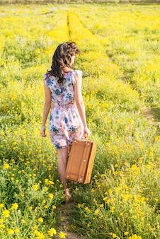 Милая молодая женщина в поле с старым чемоданом