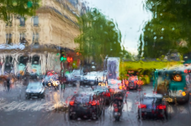 濡れたガラス越しに通りと車の眺め