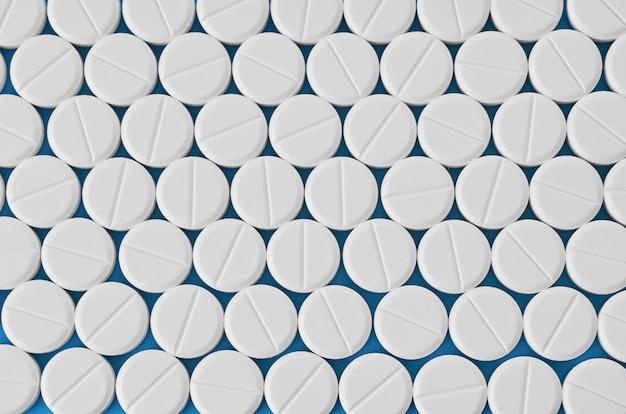 Таблетки таблетки капсулы крупным планом. на синем фоне баночка с лекарством.