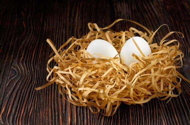 木製のテーブルに巣の形をした紙わらに白い卵。低いキー。