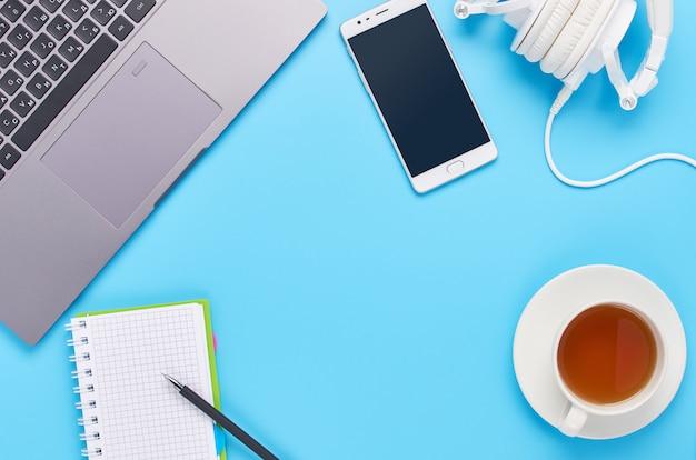Вид сверху на гаджеты на синем фоне, композиция ноутбука, белые наушники, телефон, бокал с напитком и ключи от машины