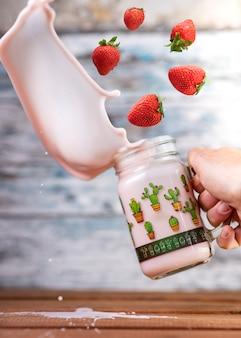 おいしいいちごのスムージーを作るためにグラスに落ちる新鮮なイチゴ。木製の壁