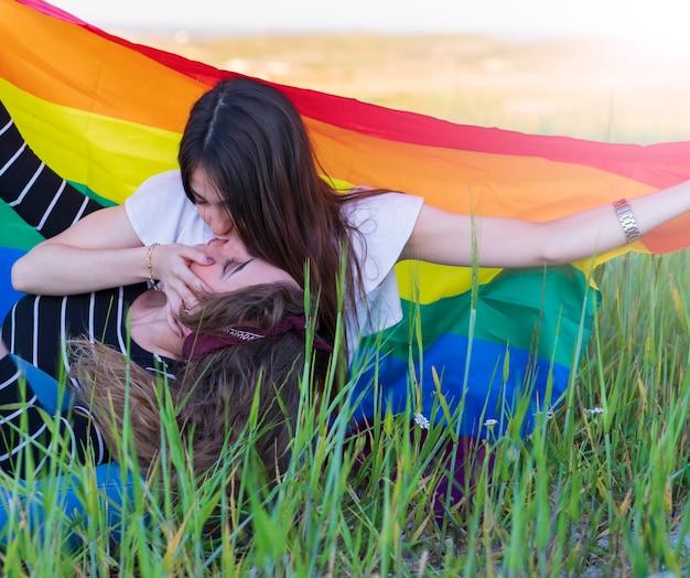 Красивая молодая пара лесбиянок нежно целуется с радужным флагом, равные права для лгбт-сообщества