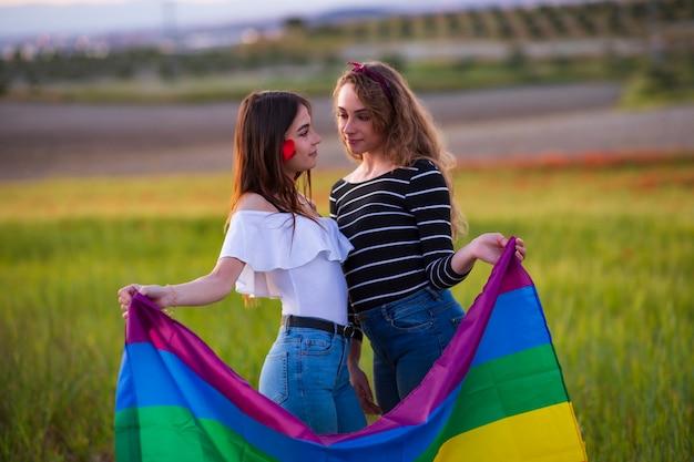 Красивая молодая пара лесбиянок с радужным флагом, равные права для лгбт-сообщества