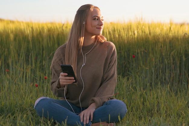 Красивая девушка с ее мобильным, слушая музыку в природе