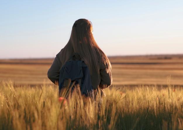バックパックを持つ女性を旅行します。日没、大麦麦畑を見ているフィールドに