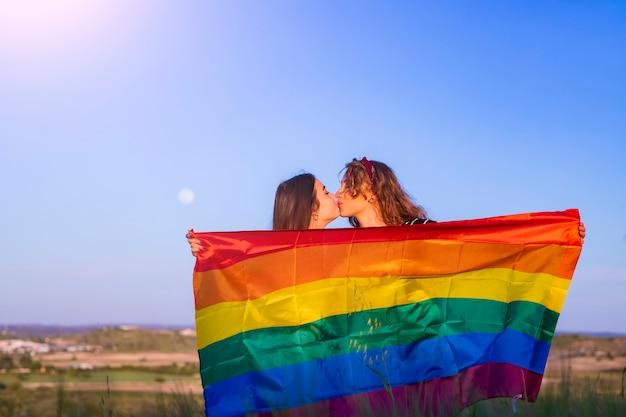ゲイの旗の前で幸せなゲイの女の子のカップルのキス