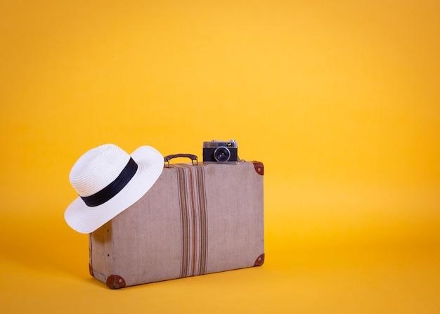 Чемодан фотоаппарат шляпа, желтый фон, концепция путешествия