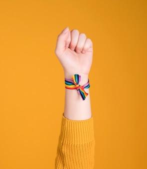Радужный браслет с поднятой рукой, лгбт, гей, на пастельно-желтом фоне