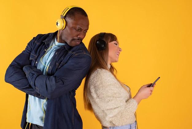 Веселая многонациональная пара стоял вместе, изолированные на, слушая музыку в наушниках, держа мобильный телефон