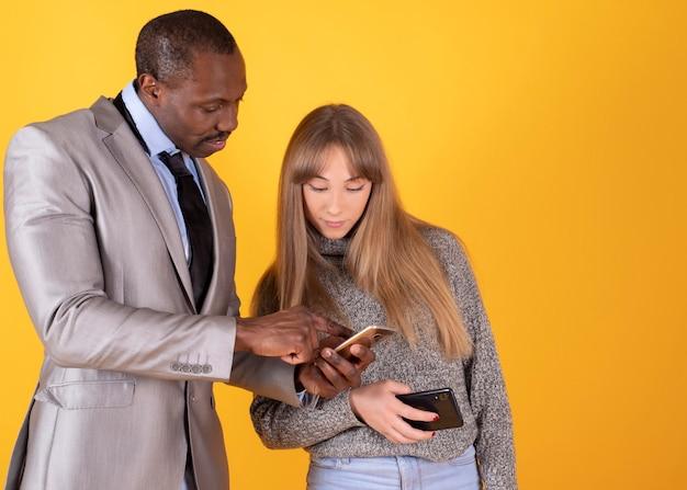 スマートフォンを使用してお互いにコンテンツを表示する幸せな混合カップル。男と女の携帯電話。ガジェットを持つ人々の概念